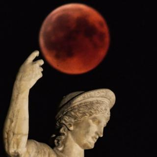 A picture shows the full moon during a 'blood moon' eclipse beside a statue of ancient Greek god Ares in central Athens on July 27, 2018