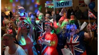 "Brexit supporters wave Union flags as the time passes 11 O""Clock at a Brexit Celebration party at Woolston Social Club in Warrington, north west England"