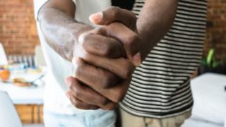 Two men hold hands