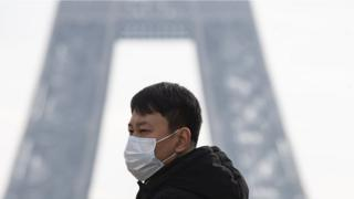 A tourist wears a face mask near the Eiffel Tower in Paris, France, 25 January 2020