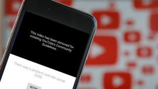 A photo illustration shows the YouTube app on a mobile phone with the message that the video has been taken down