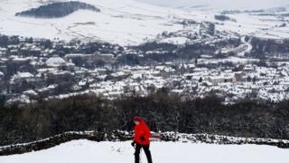 Man hiking up snowy hill with snow covered Buston in the background