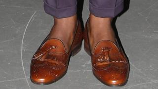 A man wearing shoes but no socks
