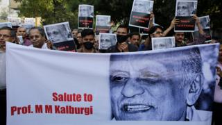 Protesters holding a banner depicting murdered writer Malleshappa Kalburgi