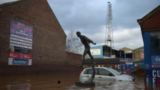 A car is partly submerged by flood waters at Carlisle United's Brunton Park in December 2015