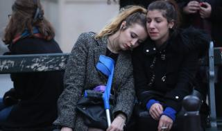 Two women pause for thought outside Le Carillon restaurant in Paris (16 Nov)