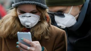 People wearing protective face masks use a smartphone on a street amid coronavirus concerns in Kiev