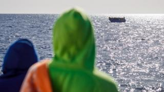 Two African migrants on the Aita Mari looking at to see at a boat full of migrants - Monday 10 February 2020