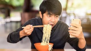 A man eating noodles while checking his mobile phone