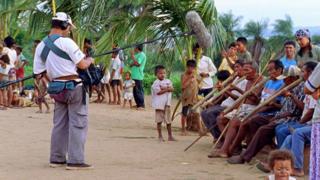 Cena da gravação do documentário 'No Caminho da Expedição Langsdorf', em uma comunidade indígena - homens estão sentados tocando um instrumento de sopro longo