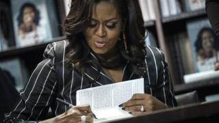 "Former US First Lady Michelle Obama signs copies of her new book ""Becoming"" at a Barnes and Noble bookstore in New York City, 30 November 2018"