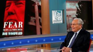 """Боб Вудворд на фоне обложки своей книги """"Страх: Трамп в Белом доме"""""""
