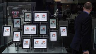 "A man passes a display of ""I love MCR"" signs in the window of an estate agent""s in Manchester"