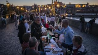 Residents dine at a long table set on the Charles Bridge