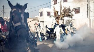 A horse and cart on a road which is being disinfected by municipal workers in Dakar, Senegal -Wednesday 1 April 2020