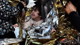 A child, covered by emergency blankets, reacts as she arrives with other refugees and migrants on the Greek island of Lesbos