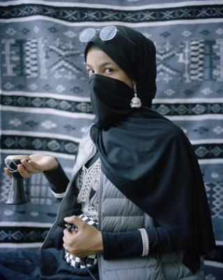 Portrait of woman wearing various cultural clothes, looking to the camera