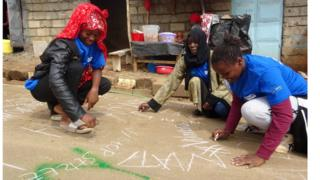 A photo of girls writing their street harassment experiences on roads