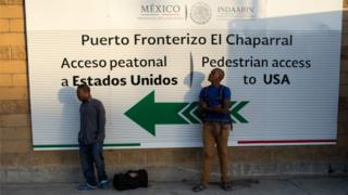 Dos haitianos esperan cerca del acceso peatonal a EE.UU. desde Tijuana.