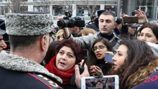 Женщина, полицейский стоящий спиной к камере. Вокруг толпа