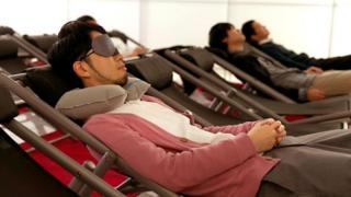 عدد من الموظفين في شركة يابانية أثناء الاستمتاع بالقيلولة