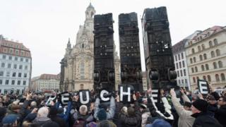 Demonstrators protest against the upturned buses sculpture in Dresden (07 February 2017)