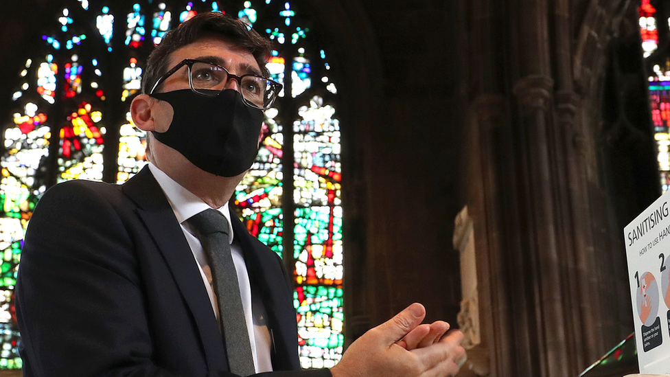 Andy Burnham sanitises his hands at Manchester Cathedral