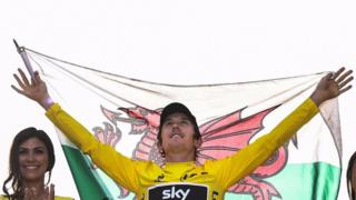 Geraint Thomas hold Welsh flag on Tour de France winner's podium