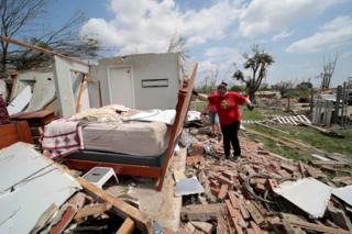 A woman searches through the rubble of a destroyed house