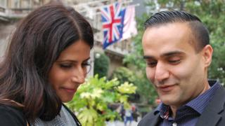 Barinder and Dilshad on a London street looking at their mobile phone
