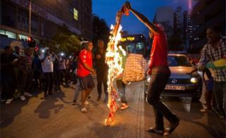 Zimbabweans living in South Africa celebrate by burning a banner with Robert Mugabe's image after President Robert Mugabe resigns, in Johannesburg, South Africa November 21, 2017.