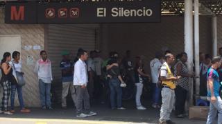Estación del metro cerrada y una fila esperando el transporte en superficie.