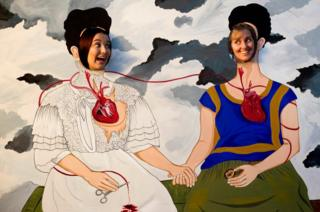 Two women pose in a Frida Kahlo cut out