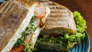 Chicken and ham sandwiches with tomatoes and arugula.