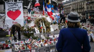 One month after the Paris attacks, people continue to gather in front of the memorial of candles and flowers for the victims of the 13 November Paris attacks, on Place de la Republique in Paris, France, 13 December 2015