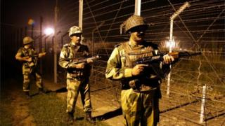 A picture made available on 03 October 2016 shows Indian Border Security Force (BSF) soldiers standing guard during a night patrol near the fence at the India-Pakistan International Border at the outpost of Akhnoor sector, about 40 km from Jammu,