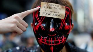 "A masked anti-government protester points to a sign on his forehead which says ""stand with freedom, stand with Hong Kong"""