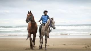 Lubabalo rides horses on the beach
