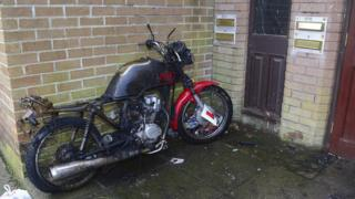 A charred motorbike that was set on fire outside the flats
