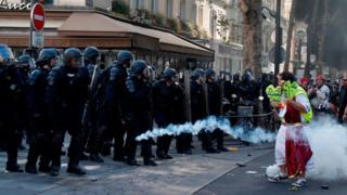 A line of riot police firing tear gas at a protester