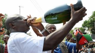 Man dey drink from big bottle of Champagne