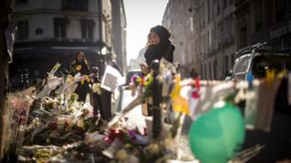 A person cries as she stands at a makeshift memorial for a tribute to the victims of a series of deadly attacks in Paris, in front of the Casa Nostra restaurant in Paris on November 13, 2015