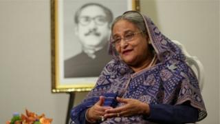 شيخة حسينة وخلفها صورة والدها، مجيب الرحمن، اول رئيس جمهورية لبنغلاديش