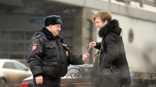 Полицейский угощает юношу сигаретой