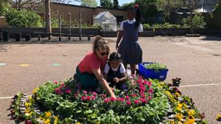 Key worker pupils and staff make a rainbow of flowers