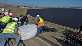 Workers release plastic 'shade balls' into a reservoir in Los Angeles