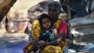 A Sri Lankan Tamil woman and child look on in the eastern town of Muttur on August 22, 2015. Sri Lankan President Maithripala Sirisena visited the region to return land to some 205 families whose properties were occupied by security forces during the Tamil separatist war that ended in May 2009.