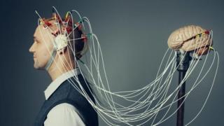 Una persona con cables conectados de su cabeza a un cerebro de plástico