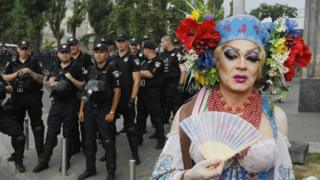 A drag queen poses in front of police