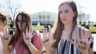 ホワイトハウスの前で、「撃たないで」と手に書き抗議する若者たち